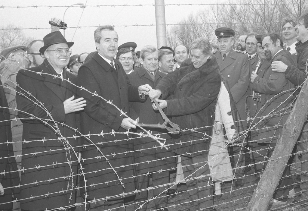 """Hier sind Alois Mock und Jiří Dienstbier, die damaligen Außenminister Österreichs und der Tschechoslowakei, dabei zu sehen wie sie den """"Eisernen Vorhang"""" bei Laa/Thaya durchtrennen."""